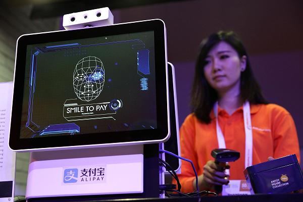 A woman standing behind a facial recognition system