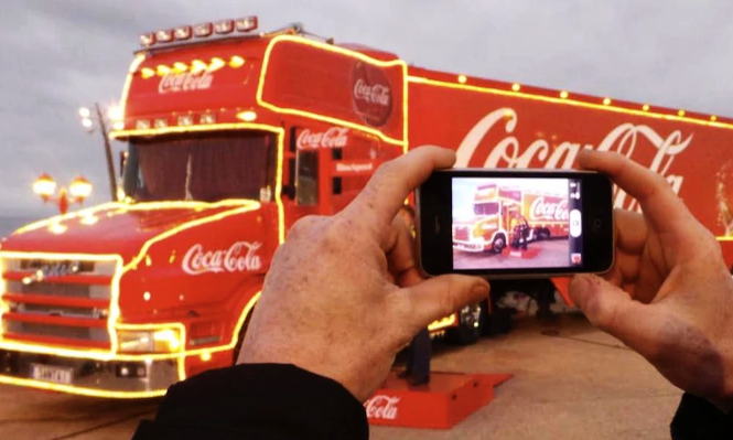 A person taking a photo of a Coca Cola truck adorned with christmas lights